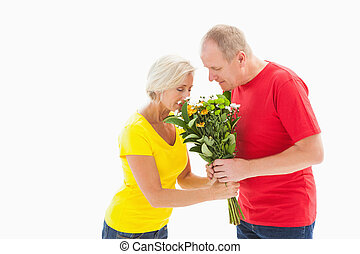 Mature man offering his partner flowers on white background