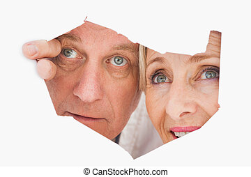 Older couple looking through rip on white background