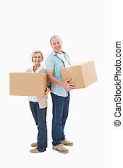 Older couple smiling at camera holding moving boxes on white...