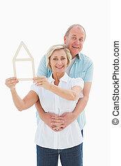 Happy older couple holding house shape