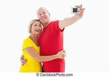 Happy mature couple taking a selfie together on white...