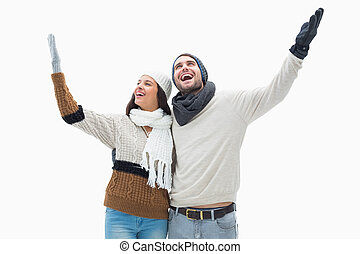 Attractive young couple in warm clothes with arms up