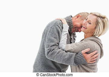 Happy mature couple in winter clothes on white background