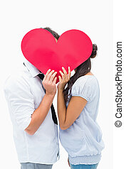 Couple covering their kiss with a heart on white background