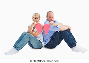 Sad mature couple holding a broken heart on white background