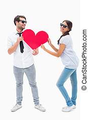Hipster couple smiling at camera holding a heart on white...