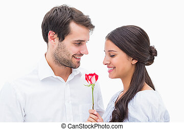 Handsome man offering his girlfriend a rose on white...