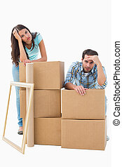 Stressed young couple with moving boxes on white background