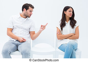 Man pleading with angry girlfriend on white background