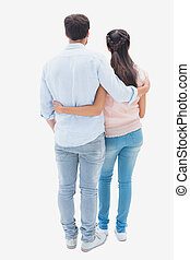 Attractive young couple standing with arms around on white...