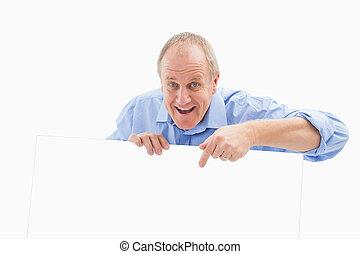 Mature man smiling at camera and pointing
