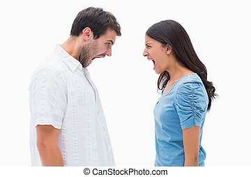 Angry couple shouting at each other on white background