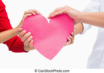 Couples hands holding pink heart on white background