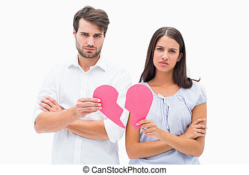 Upset couple holding two halves of broken heart on white...