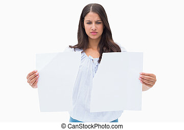 Upset brunette holding torn paper on white background