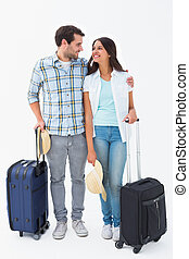 Attractive young couple going on their holidays on white...