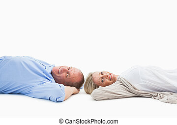 Mature couple lying and smiling on white background