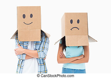 Young couple wearing sad face boxes over head on white...