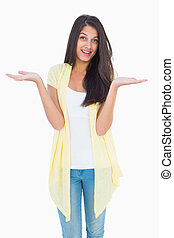Happy casual woman shrugging her shoulders on white...