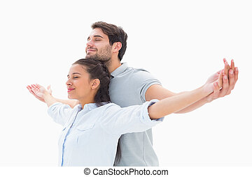 Cute couple standing with arms out on white background