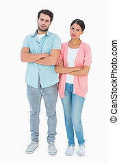 Serious couple with arms crossed on white background