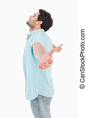 Happy casual man standing with arms out on white background