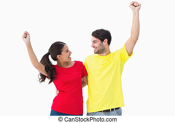 Excited couple cheering in red and yellow tshirts on white...