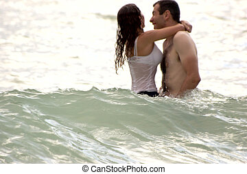 young couple playing in ocean