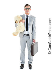 Handsome businessman holding briefcase and teddy on white...