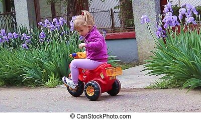 Girl enjoying riding her tricycle - Young girl rides bicycle...