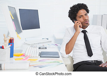 Serious businessman working at his desk on the phone
