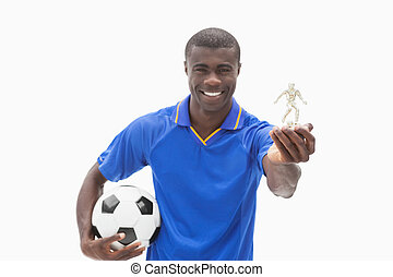 Football player in blue holding ball and figurine on white...