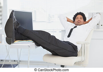 Businessman relaxing in his swivel chair with feet up in his...