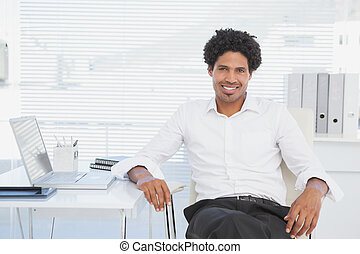 Handsome casual businessman smiling at camera in his office