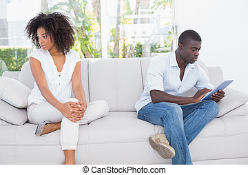 Attractive couple not talking on the couch at home in the...