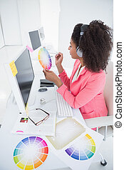 Casual graphic designer working at her desk in her office