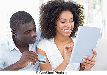 Attractive couple using tablet together on sofa to shop...