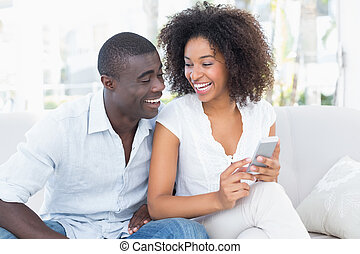 Attractive couple sitting on couch together looking at...