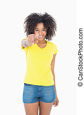 Pretty girl in yellow tshirt and denim hot pants pointing at...