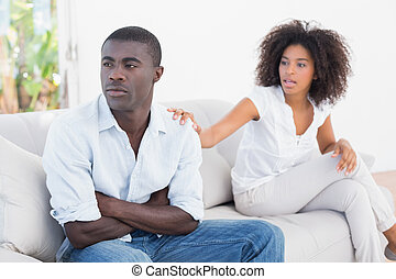 Attractive couple having an argument on couch at home in the...