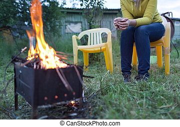 Woman with tea near the fire in the yard