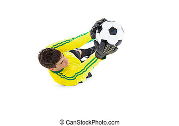 Goalkeeper in yellow holding ball on white background