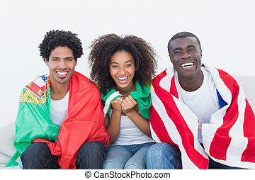 Football fans sitting on couch with flags on white...