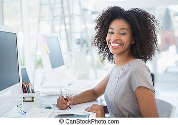Young pretty designer smiling at camera at her desk in her...