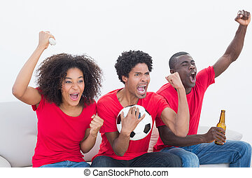 Football fans in red sitting on couch cheering on white...
