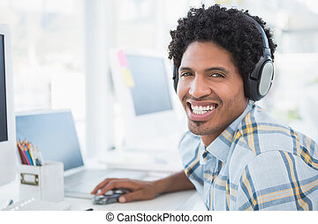 Young designer listening to music as he works in his office