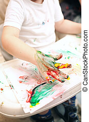 Boy painting with finger-paints - Little boy painting with...