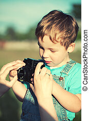 Mother helping her son to make his first photos