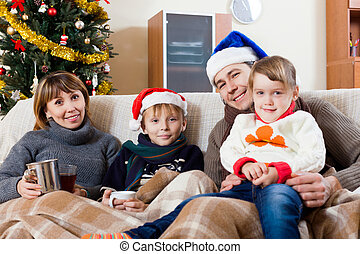 Family of four on sofa at home