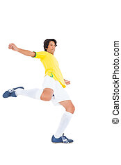 Football player in yellow kicking on white background